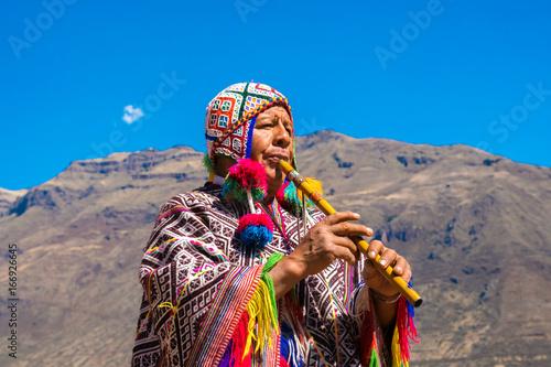 Fotografie, Obraz  Peruvian man playing a flute, Sacred Valley, Cusco, Peru