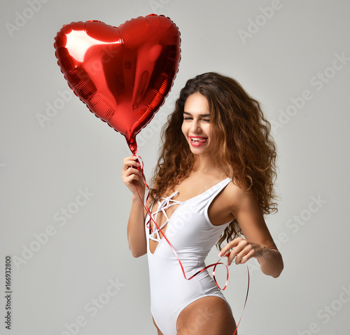 Photo  Young happy girl with red heart balloon as a present for birthday party smiling