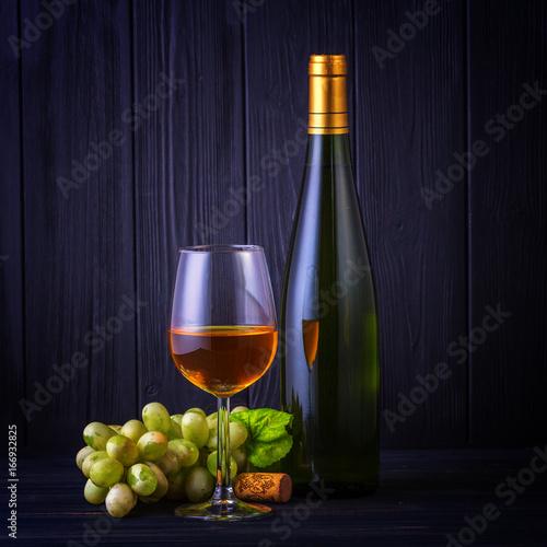 kieliszek-bialego-wina-z-butelki-i-winogrona-na-tle-ciemnych-desek