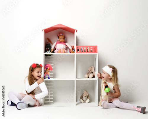 Fototapeta Baby Girls child Kids playing with doll house for mini furniture toys and dolls