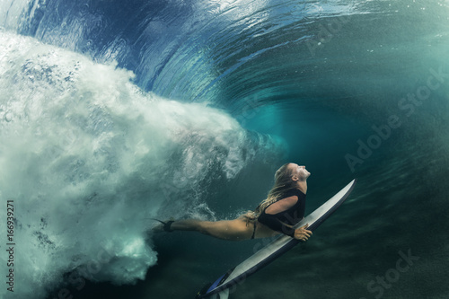 Photo  A blonde surfer girl underwater doing duck dive holding surfing board left behin
