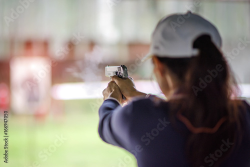Tela gun holding in hand of woman in practice shooting in martial arts for self defen