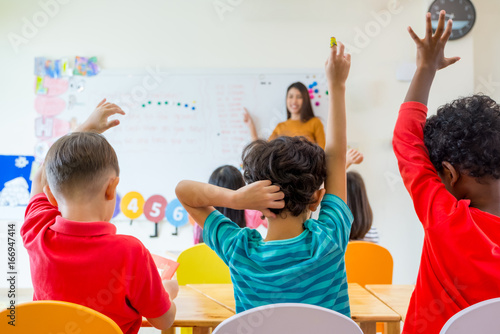 Preschool kid raise arm up to answer teacher question on whiteboard in classroom Wallpaper Mural