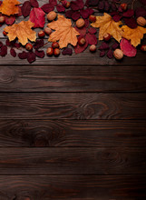 Flat Lay Frame Of Autumn Crimson And Yellow Leaves, Hazelnuts, Walnuts And Apples On A Dark Wooden Background.