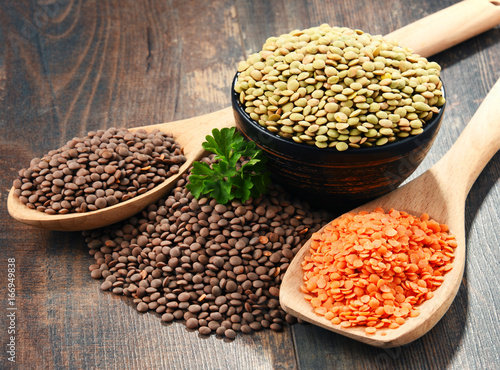 Composition with bowl of lentils on wooden table