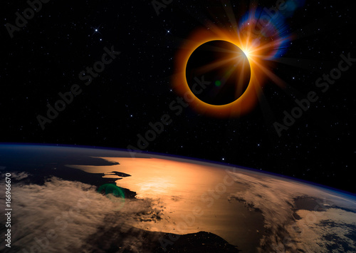 Solar eclipse with orange halo over the planet Earth, on dark starry sky
