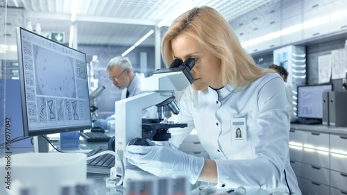 Fotografia  Female Research Scientist Looks at Biological Samples Under Microscope
