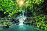 Beautiful mountain rainforest waterfall with fast flowing water and rocks, long exposure. Natural seasonal travel outdoor background with sun shihing