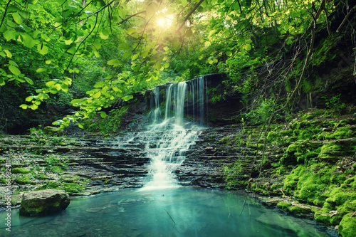 Poster Cascades Beautiful mountain rainforest waterfall with fast flowing water and rocks, long exposure. Natural seasonal travel outdoor background with sun shihing