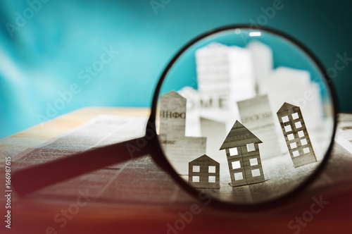 Fotografía  Magnifying glass in front of an open newspaper with paper houses