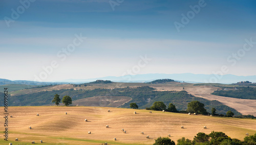 Foto op Canvas Blauwe jeans Beautiful harmonious landscape with twisted haystacks in the field in Tuscany, Italy in sunlight. (Crop, welfare - concept)
