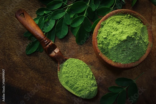 Photo Overhead view of Moringa powder in an earthern pot on dark wooden background