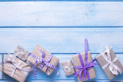 Festive gift boxes with presents on blue wooden background.
