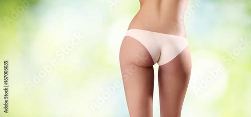 Zdjęcie XXL pośladki kobiety widzieć od behind na zieleni zamazywali tło, ciało opieki pojęcie