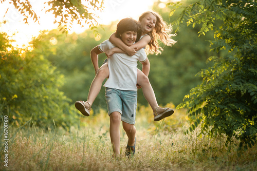 Little boy carries girl on his back.
