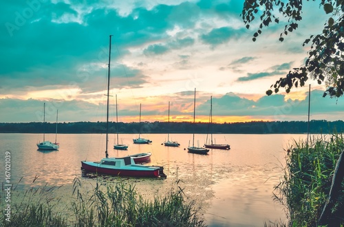 Poster Pleine lune Summer evening landscape. Boats on the lake and colorful sky.