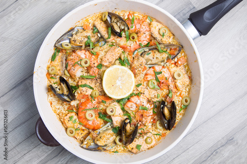 Paella with tiger shrimps, mussels, salmon and olives. Traditional Spanish dish.