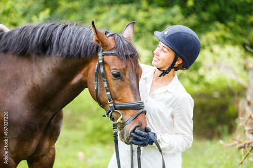 Fototapeta Young smiling rider woman in helmet holding bay horse by bridle obraz