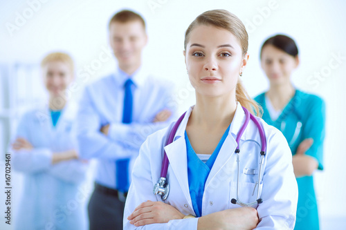Foto  Attractive female doctor with medical stethoscope in front of medical group