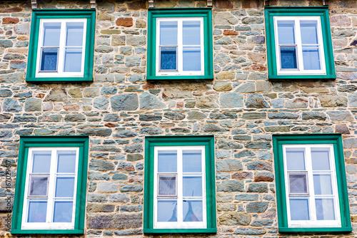 Fotografie, Obraz  Closeup of european architecture stone building with green window frames