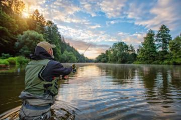 Sportski ribar lovi ribu. Ribolov na otvorenom u rijeci