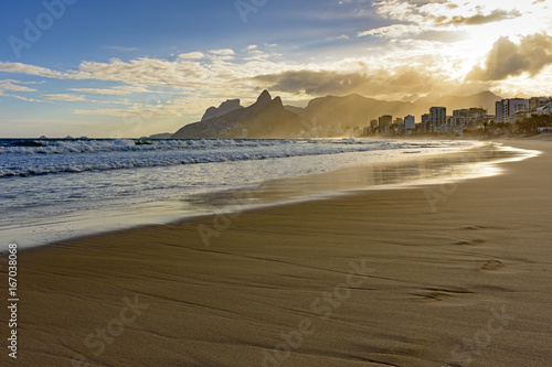Summer sunset at Ipanema beach in Rio de Janeiro with the light crossing the bui Wallpaper Mural