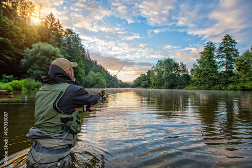 Fototapeta Sport fisherman hunting fish. Outdoor fishing in river