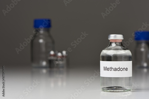 Photo  A ampoule of methadone (English label) stands on white surface against gray background on the right
