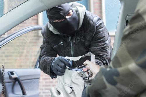 Photo Ein Räuber versucht eine Handtasche aus einem Fahrzeug zu entwenden