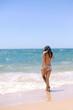 Attractive woman bathing playfully on a sunny summer holiday, joyful, coastal outdoors background. Travel lifestyle enjoying the sun on beach shore.