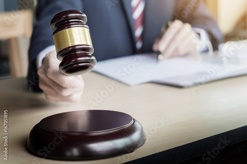 Fotografija  Male Judge In A Courtroom Striking The Gavel on sounding block
