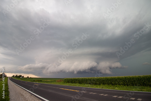 A low wall cloud hangs under the base of a large supercell thunderstorm in Iowa.