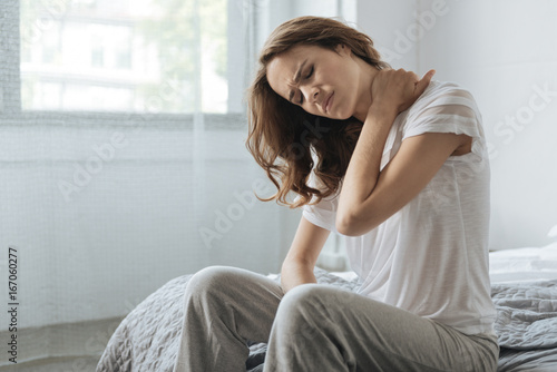 Moody young woman holding her neck Wallpaper Mural