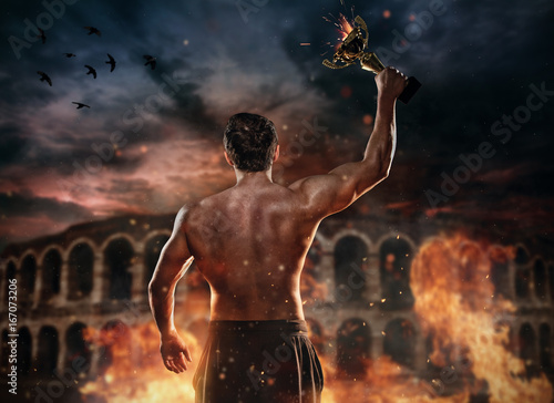 Fotografia  Back view of muscular man holding burning trophy cup, antique colosseum on background