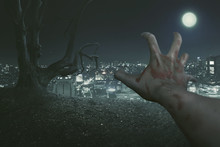 Halloween Concept,  The Point Of View Of The Zombie's Right Hand, With The Background Of An Old Tree And A City Lit By The Light Of The Full Moon.