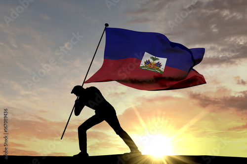 Wallpaper Mural Haiti flag being pushed into the ground by a male silhouette