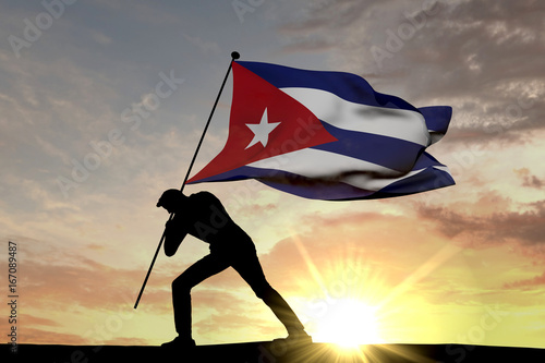 Cuba flag being pushed into the ground by a male silhouette Canvas Print