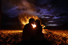 Kissing Couple Sits Before A Fireplace On The Beach