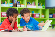 Two Boy Kid Lay Down On Floor And Reading Tale Book  In Preschool Library,Kindergarten School Education Concept