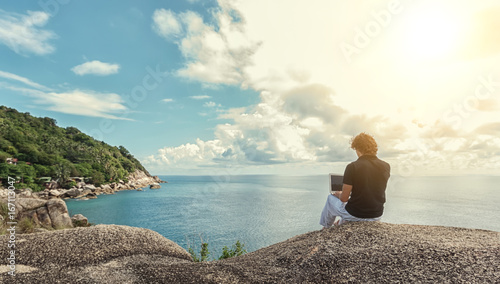 Fotografie, Obraz Young man, the freelancer sits on a high cliff over the sea and works remotely