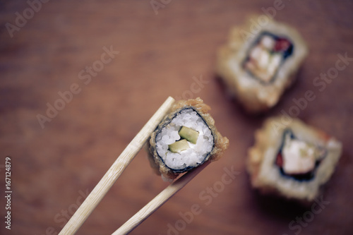 Fotografie, Obraz  Japanese sushi rolls on a wooden stand. Japanese food.