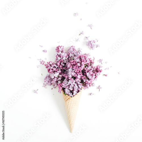 Waffle cone with lilac flower bouquet on white background. Flat lay, top view floral background.