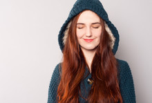 A Beautiful Happy Woman With Long Hair Dressed In A Warm Knitted Blue-green Sweatshirt Or Coat With A Hood Warmed With White Fur. She Closed Her Eyes And Smiled. Warm Clothes For The Coming Autumn.