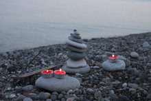 Sea Pebble Tower On The Beach At Sunset, With Candles Close Up.