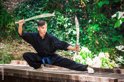 Keuken foto achterwand Vechtsport Young man practicing martial arts with a sword
