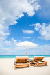 Beach chairs and umbrella on exotic tropical white sandy beach
