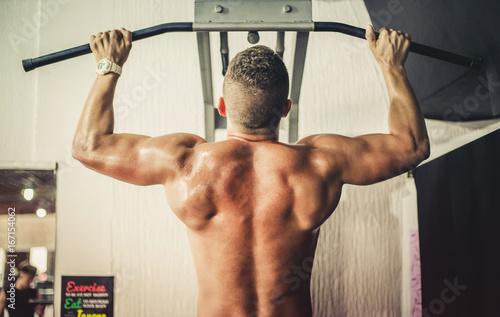 Plakat Atrakcyjny młody mięśniowy mężczyzna pracujący out jego plecy przy gym