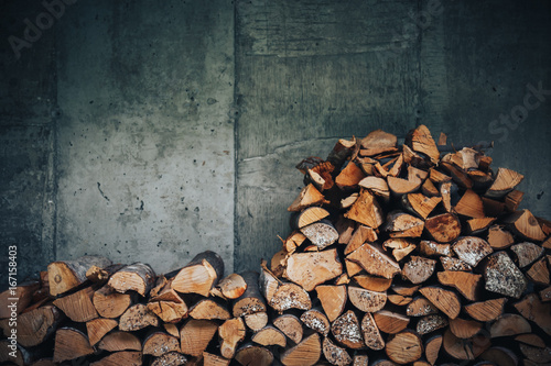 Photo Stands Firewood texture chopped logs for winter fire. Pile of firewood against old wooden fence