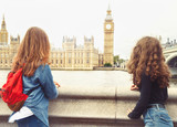 Fototapeta Londyn - Two trendy teenage girls look at Big Ben, London