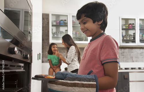 Boy baking cup cakes in tray with family